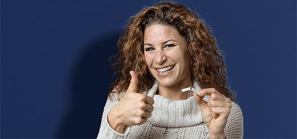 Eine junge Frau freut sich den Ausstieg aus der Rauchsucht geschafft zu haben