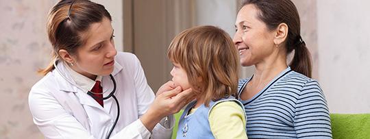 Eine Ärztin tastet die Mandeln eines Kleinkindes ab