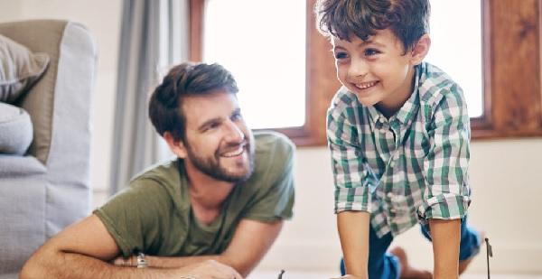 Ein Vater und sein Sohn spielen auf dem Fußboden ihrer Wohnung.