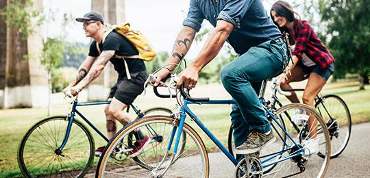 Eine Gruppe junger Menschen fährt mit Fahrrädern eine Straße entlang
