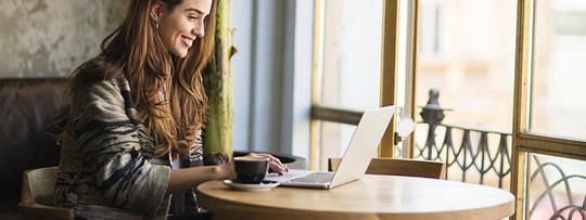Frau sitzt vor einem Laptop und meldet sich gerade im Online-Portal Meine KNAPPSCHAFT an.