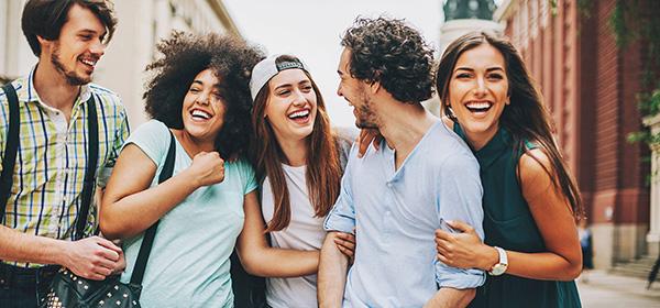 Fünf junge Menschen haben sichtlich Freude während sie eine Straße entlanggehen