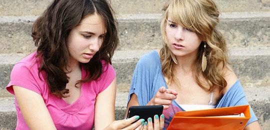 Zwei Mädchen schauen entsetzt auf ein Handy.