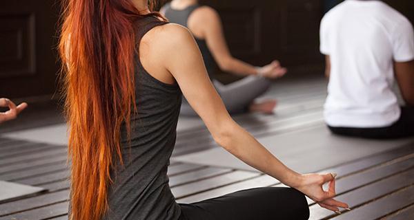 Eine junge Frau führt mit einer Gruppe Menschen Entspannungsübungen durch